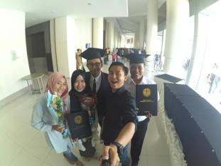 Groupie Graduation. Selfie stick was used to capture a group of students who already graduated. (photo by Abie S)