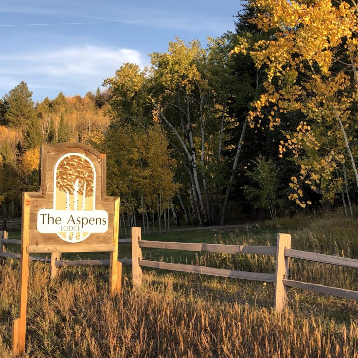 The Aspens Lodge sign with fall colors