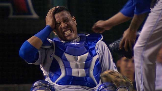 Salvador Perez. Holding his head in pain after being hit by a foul tip.