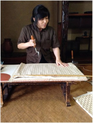 A special kind of iron is used to mark the seams. The ruler on the fabric uses the shaku, an old Japanese measure.