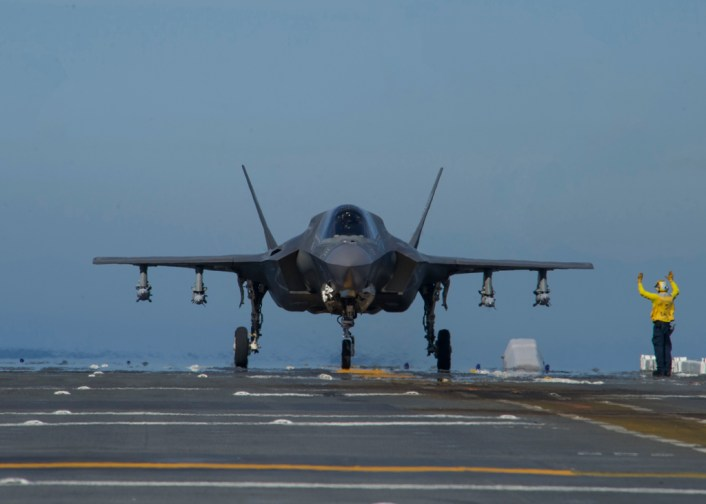 161104-N-VR008-0030 PACIFIC OCEAN (Nov. 4, 2016) A Sailor directs F-35B Lightning II aircraft on the flight deck of amphibious assault ship USS America (LHA 6) during flight operations. The F-35B short takeoff/vertical landing (STOVL) variant is the world's first supersonic STOVL stealth aircraft. America, with Marine Operational Test and Evaluation Squadron 1 (VMX-1), Marine Fighter Attack Squadron 211 (VMFA-211) and Air Test and Evaluation Squadron 23 (VX-23) embarked, are underway conducting operational testing and the third phase of developmental testing for the F-35B Lightning II aircraft, respectively. The tests will evaluate the full spectrum of joint strike fighter measures of suitability and effectiveness in an at-sea environment. (U.S. Navy photo by Petty Officer 3rd Class Kyle Goldberg/Released)