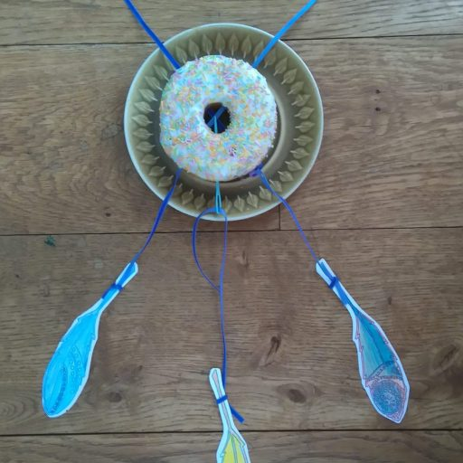 doughnut with ribbons threaded through and feathers hanging from it