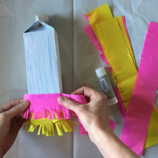 sticking homemade fringing onto a sustainable party crafts milk carton pinata