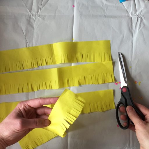 cutting tissue paper fringing for sustainable party crafts diy pinatas