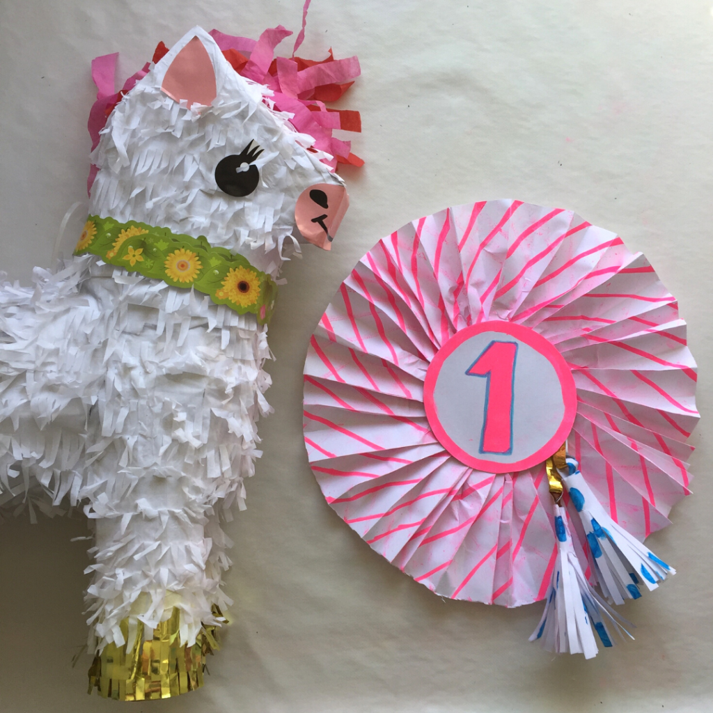 a homemade 1st birthday large celebration rosette made from a pizza box next to a unicorn pinata