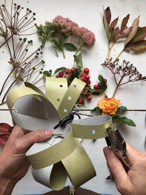 punch holes in your diy recycled cardboard fascinator - ready for inserting your foliage