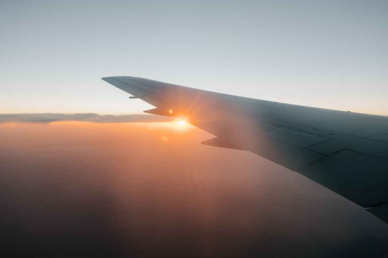 wing of airplane flying against sunset