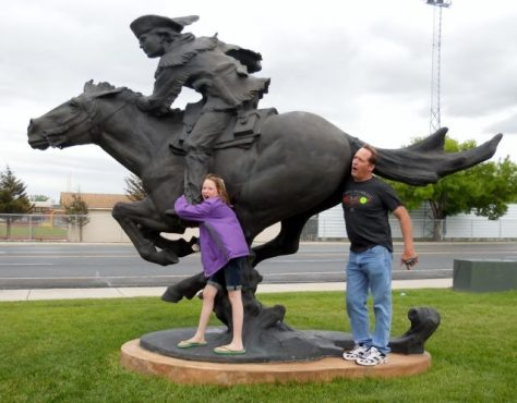 David Massender poses with Large Bronze Sculpture at the Buffalo Bill Center of the West in Cody, Wyoming