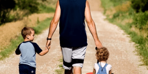 A dad walking with his two children