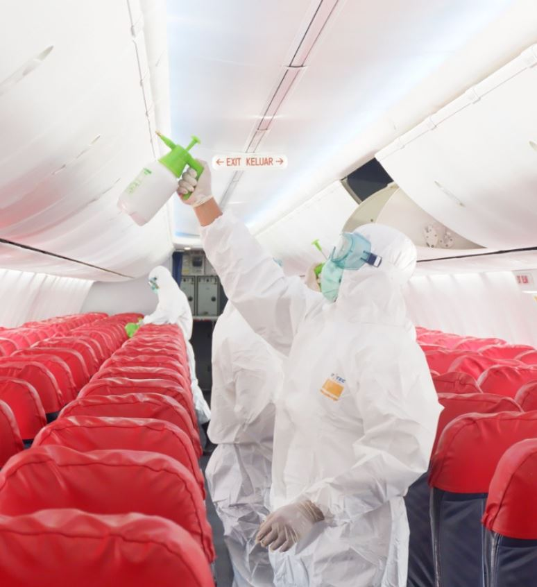 lion air plane being sanitized by men in hazmat suits