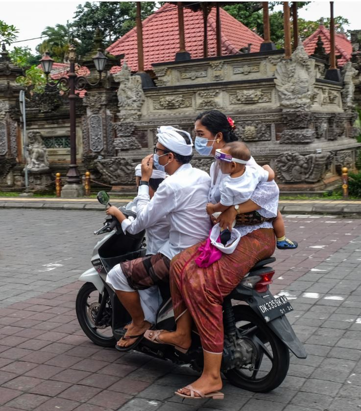 bali residents wearing masks on scooters