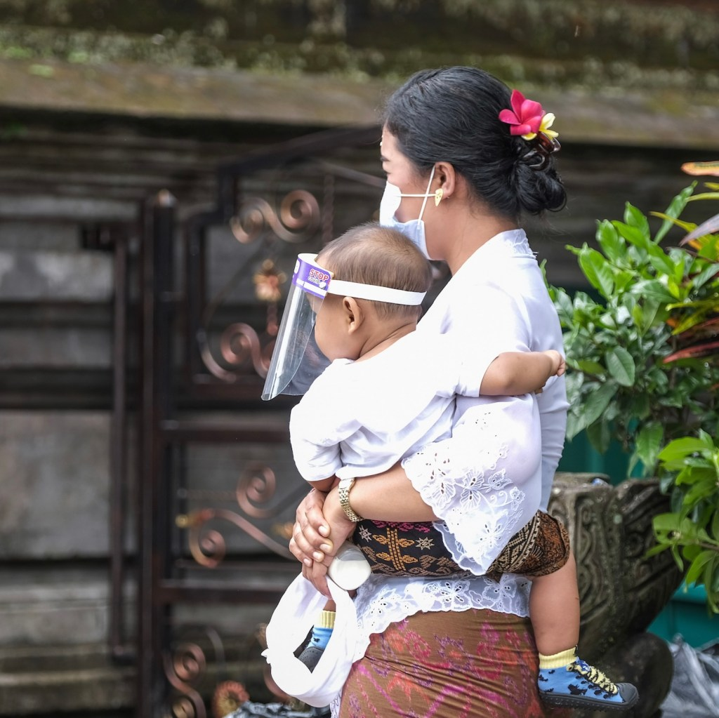 mother and baby in masks during pandemic in Bali
