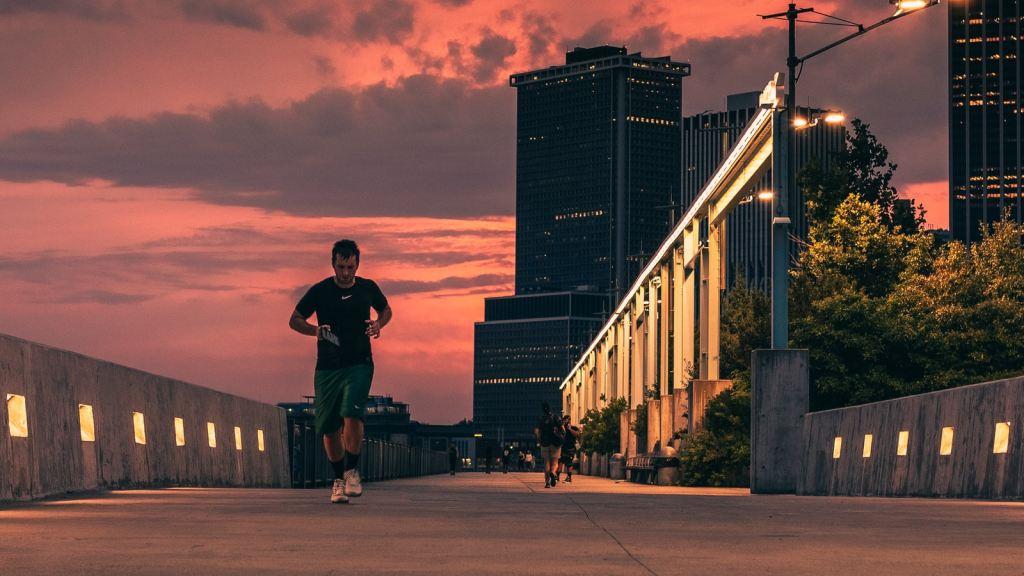 Man In Black Jacket And Black Pants Standing On Sidewalk During Sunset