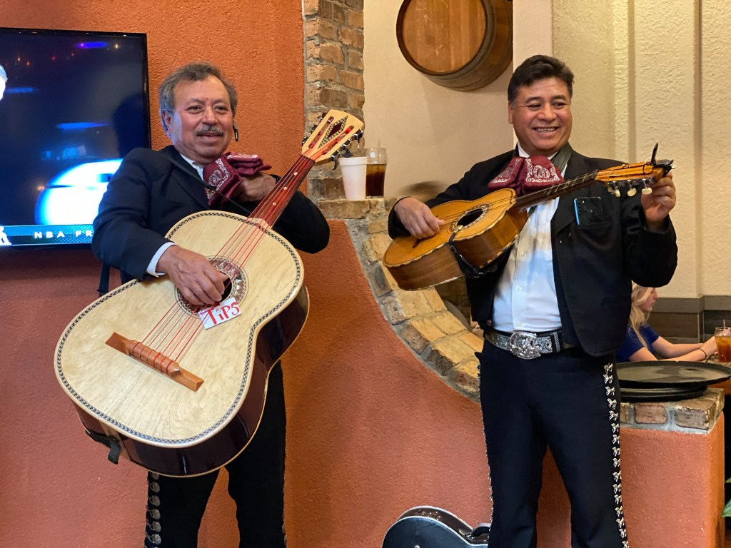 Two Men Dressed In Mexican Mariachi Attire Hold Guitars
