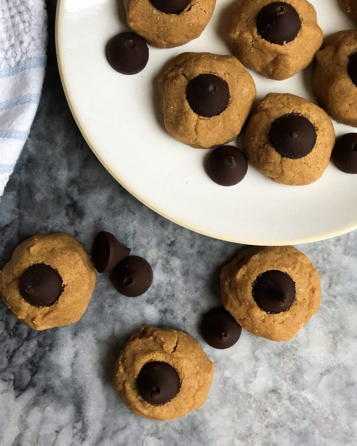 Easy and classic peanut butter blossoms with a healthy twist that remind you of childhood and make for the perfect treat at a cookie exchange! Slightly sweetened with maple syrup, they're the perfect healthy treat for Santa too!