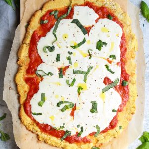 drizzle of olive oil on paleo margherita pizza