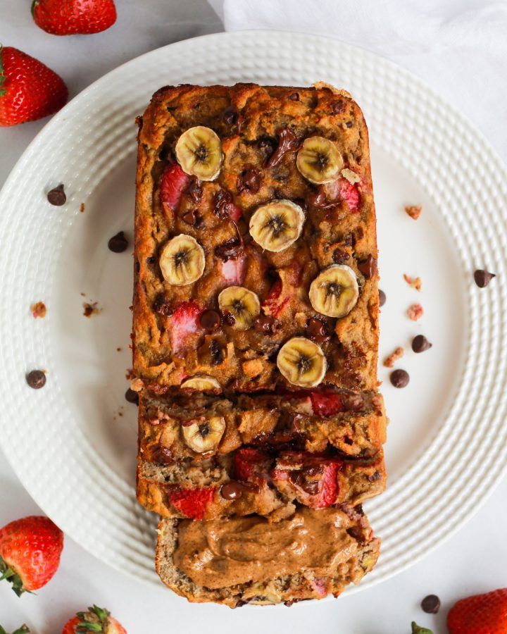 banana bread sliced with chocolate chips and strawberries on a white plate