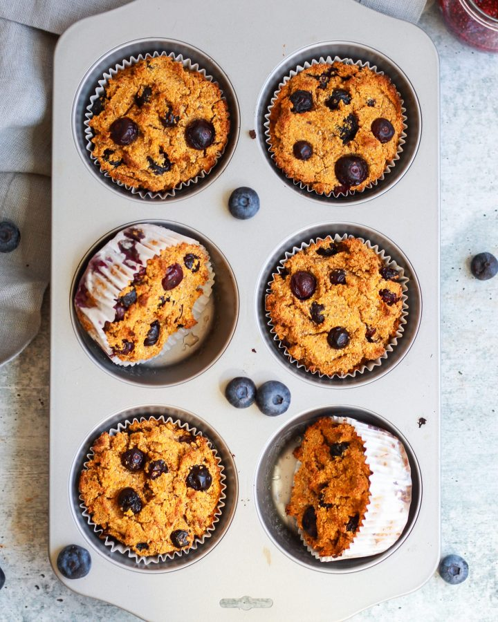 muffin tin with blueberry muffins, a few turned over