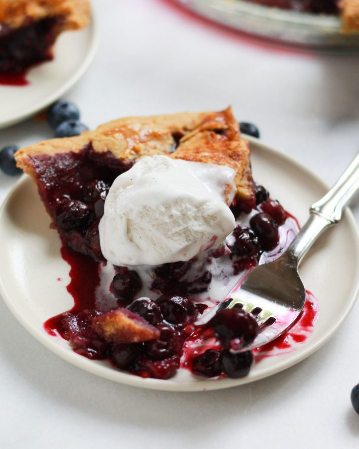 slice of blueberry pie with a bite taken out and ice cream on top