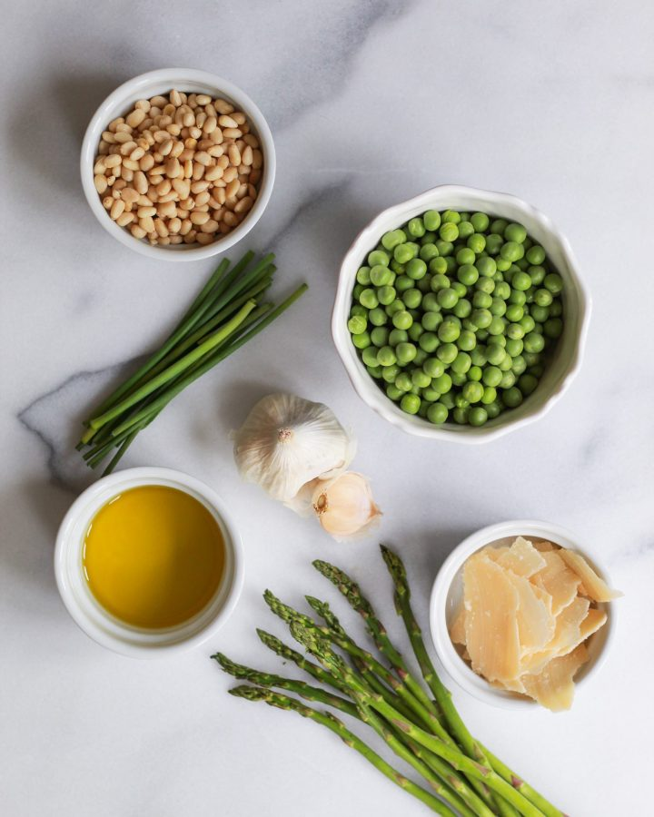 marble slab with peas, asparagus, pine nuts, olive oil, garlic, and parmesan