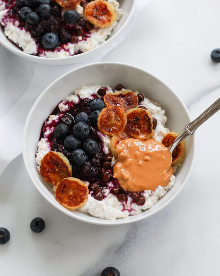 oatmeal bowl with spoon of peanut butter on white marble