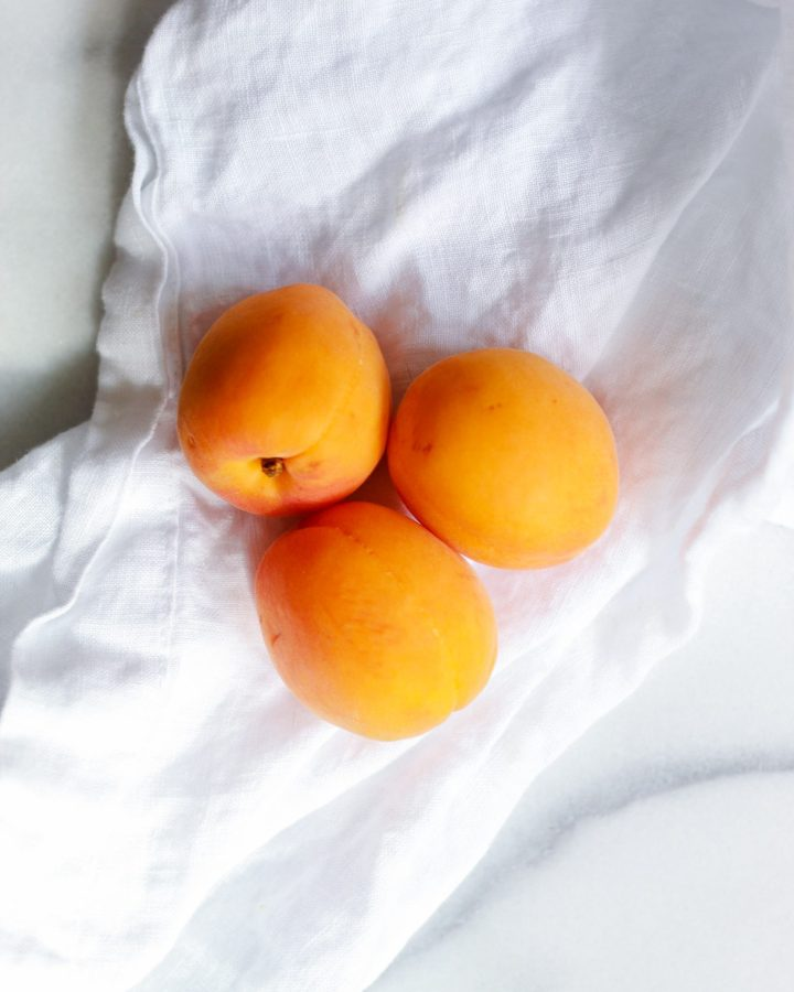 three apricots on a white cloth