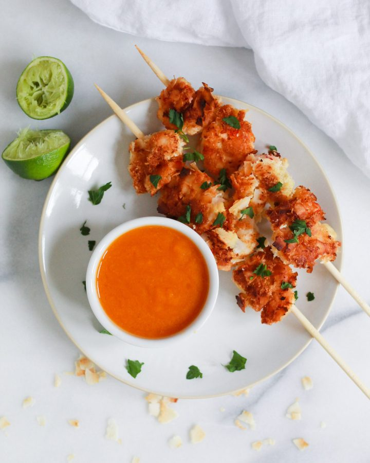plate with coconut shrimp, orange dipping sauce, and limes