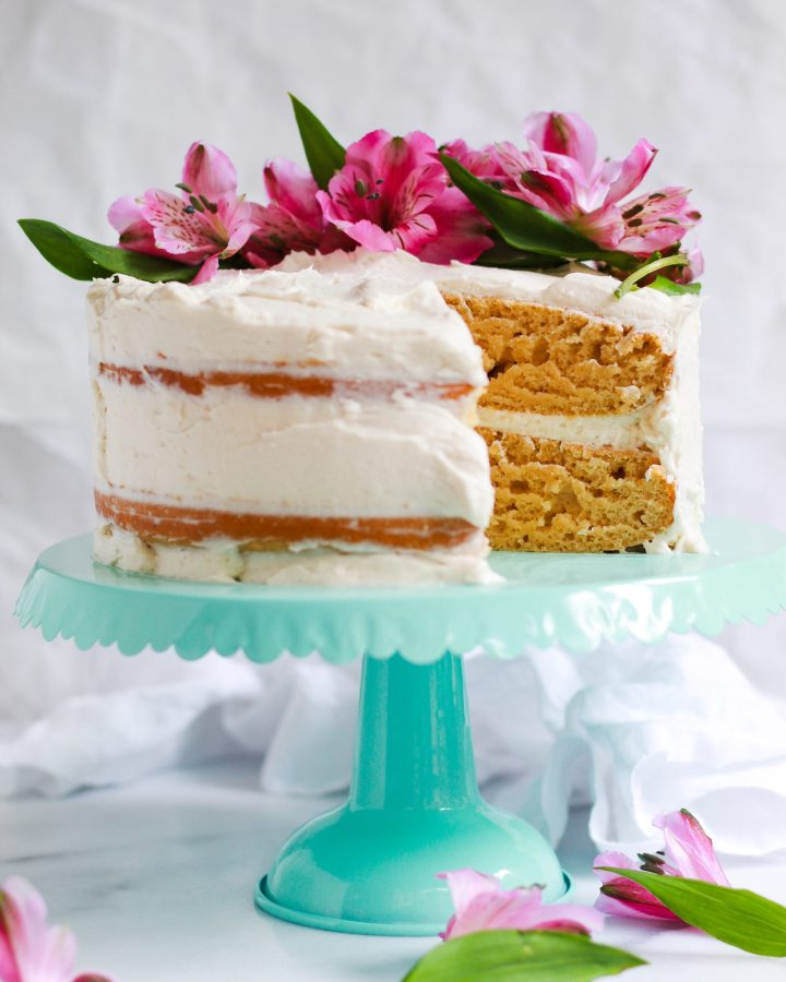 sliced vanilla cake with pink flowers on turquoise cake stand