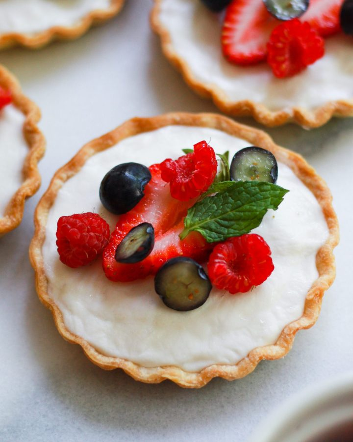 close up of single vegan fruit tart topped with berries and mint