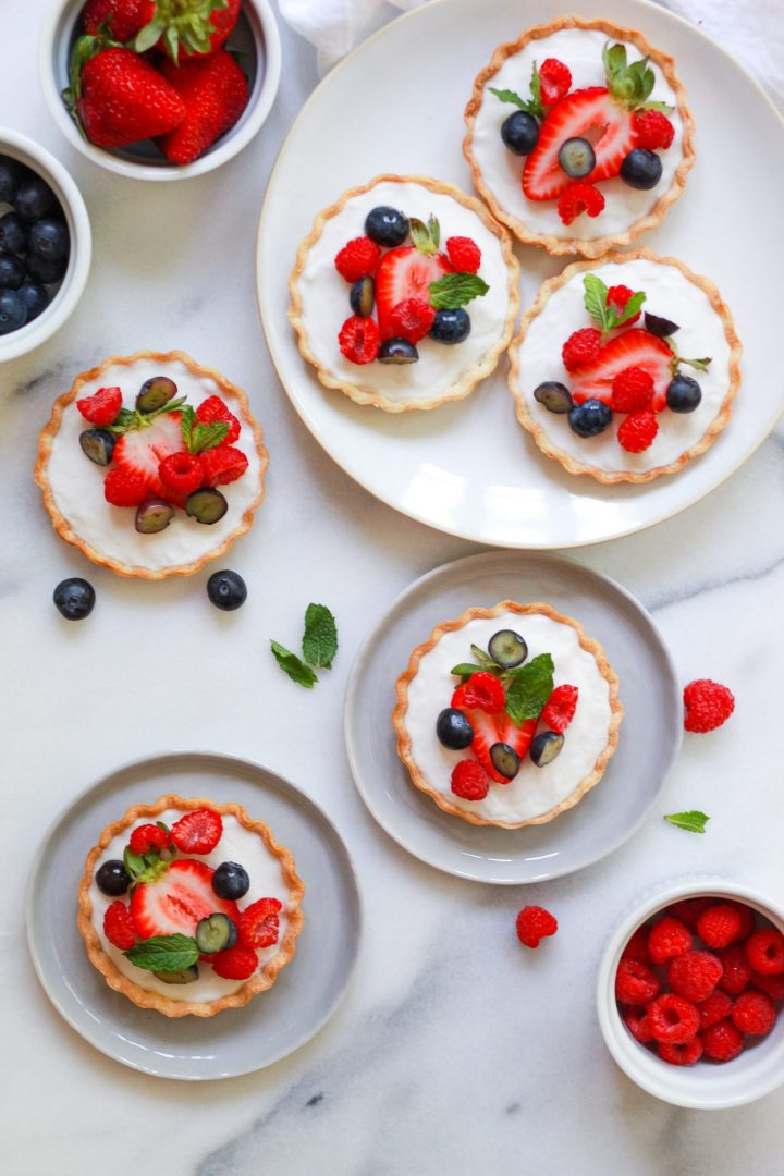 marble table with six mini fruit tarts with fresh berries