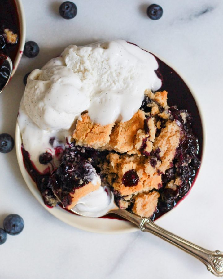 plate of blueberry cobbler with ice cream