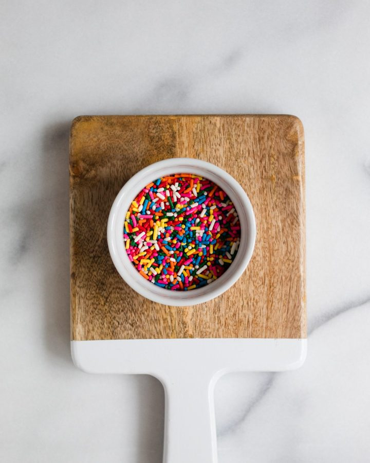 bowl of rainbow sprinkles on cutting board