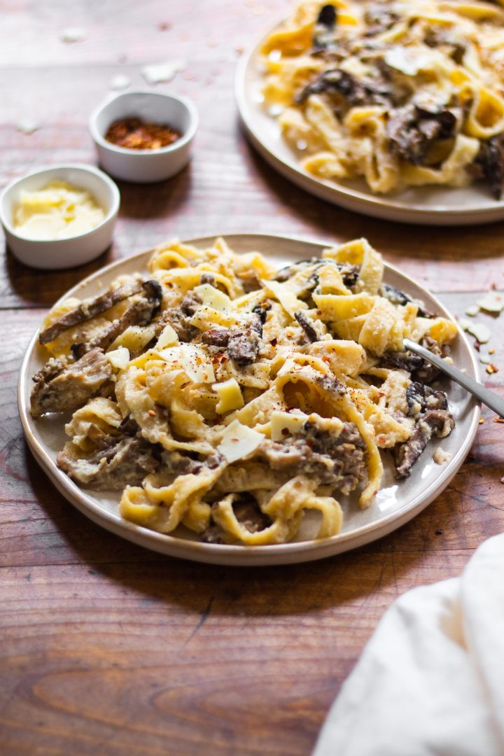 plates of vegan cauliflower Alfredo and fettuccine pasta