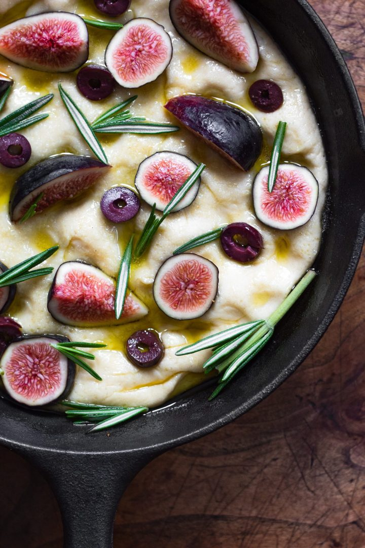 focaccia dough topped with figs, rosemary, and olives in skillet
