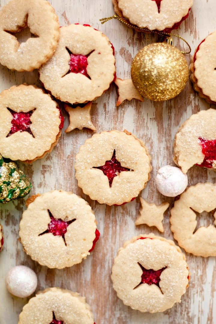 many linzer cookies on wooden board