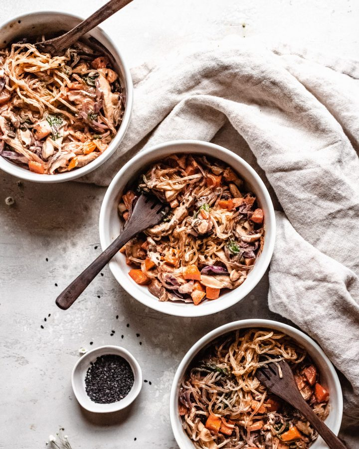 three bowls of vegan lo mein with wooden forks