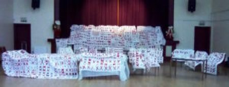 whit3e quilts embellished with pairs of red X's are draped over chairs and tables in the Coxhoe Village Hall in the U.K.