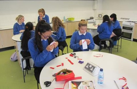 Wearing the blue sweaters of their school uniform, students of the Walgrave School in the United Kingdom use needle and thread to stitch red fabric in the shape of two red X's to a base of white fabric