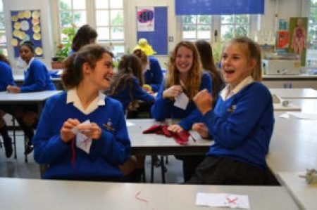 Teenage students of the Waldegrave School in the United Kingdom smile as they use red fabric to make pairs of red X's that are then stitched on a white base to become blocks for The 70273 Project