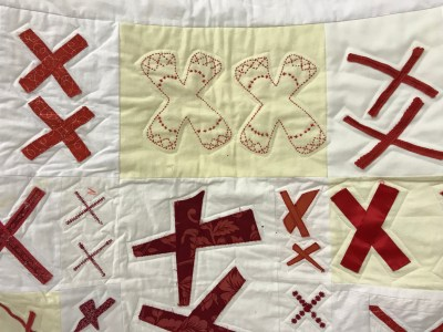 closeup photo of a quilt made of pairs of red X's stitched to a white and beige background