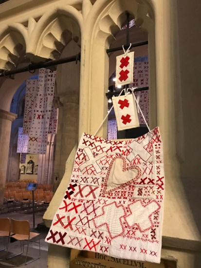 White quilts covered with pairs of red X's on display in an ancient cathedral