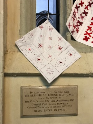 a small quilt made of pairs of red X's sewn onto white fabric