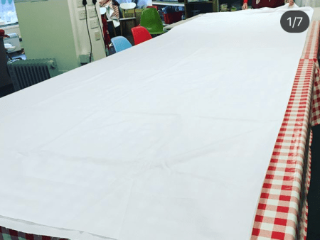a large table is covered with red and white checked table cloths and on top of the tablecloth is an expanse of white fabric