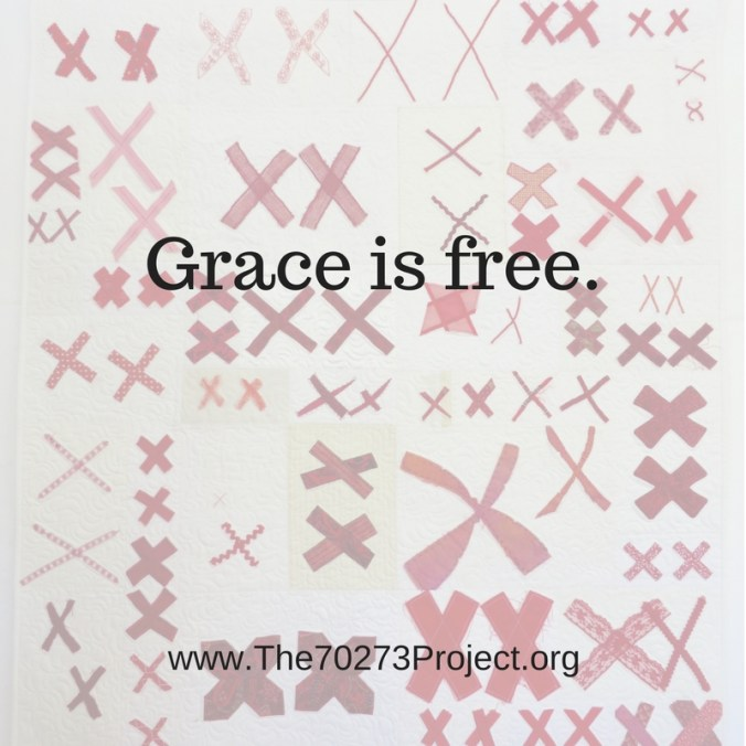 "The words ""Grace is Free"" embellish a white quilt covered with pairs of red X's in the background."
