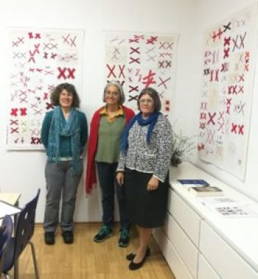 women stand in front of 3 quilts made with pairs of red X's on a white background