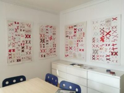 four quilts of The 70273 Project made in Dachau, Germany. White quilts covered with pairs of red X's.