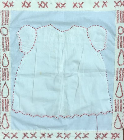 white baby christening gown sewn onto a white quit base, surrounded with pairs of red X's forming teardrops and streams of teardrops