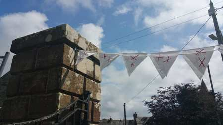 buildings and bunting bearing two red X's