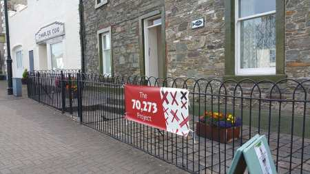 a black wrought iron fence in front of a stone building has a 70273 Project banner hanging on it