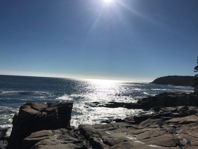 sun shining in blue sky over ocean surrounded by rocks